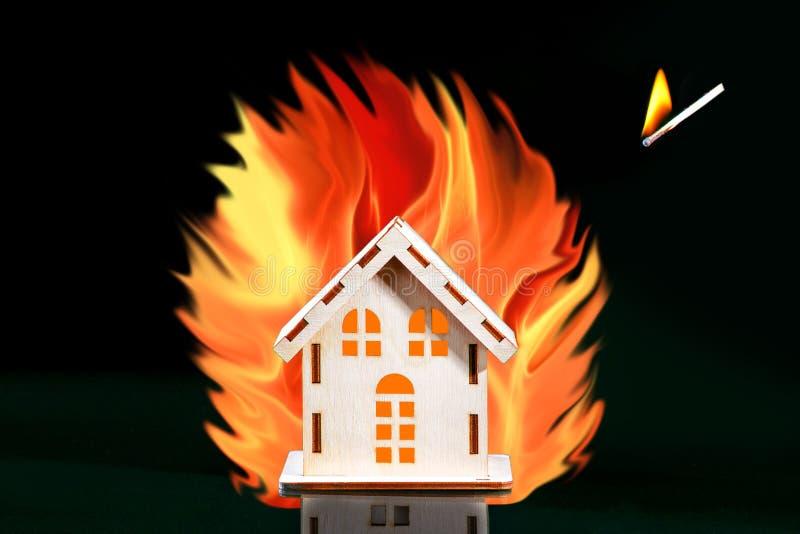 Zaogniony dopasowanie spada na domu wśrodku duży ogień, asekuracyjny pojęcie dla niebezpieczeństwa Pojęcie Bawić się Z ogieniem zdjęcie royalty free