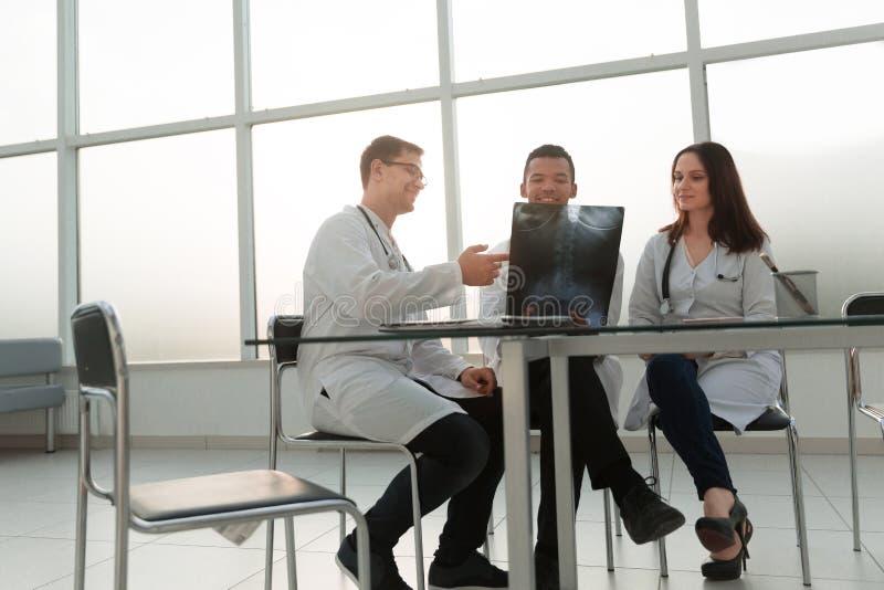 Zaopatrzenie medyczne siedzi blisko stołowych i sprawdzają rezultatów promieniowanie rentgenowskie zdjęcia royalty free