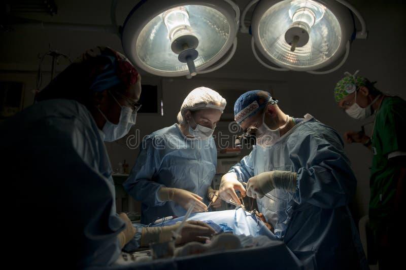 Zaopatrzenie medyczne wykonuje chirurgicznie operację w jaskrawej nowożytnej sala operacyjnej obrazy royalty free