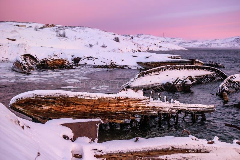Zapadnięci statki blisko śnieżnego wybrzeża w Teriberka, Murmansk region, Rosja obraz stock