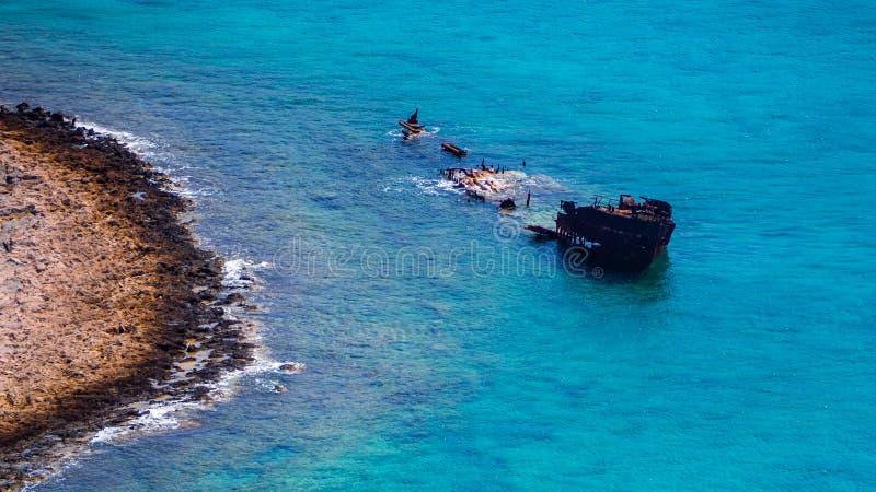 Zapadni?ty statek blisko skalistego brzeg - pi?kna tropikalna b??kitne wody obrazy royalty free