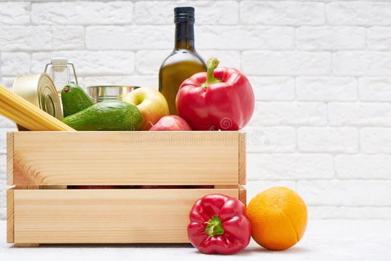 Zapasy żywności w drewnianym pudełku Warzywa, olej, owoce, żywność w puszkach, makarony Dawstwo, dostarczanie żywności, koronawir obraz stock