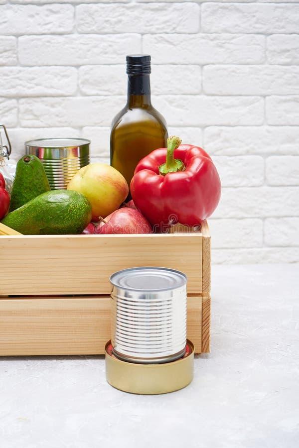 Zapasy żywności w drewnianym pudełku Warzywa, olej, owoce, żywność w puszkach, makarony Dawstwo, dostarczanie żywności, koronawir obrazy stock