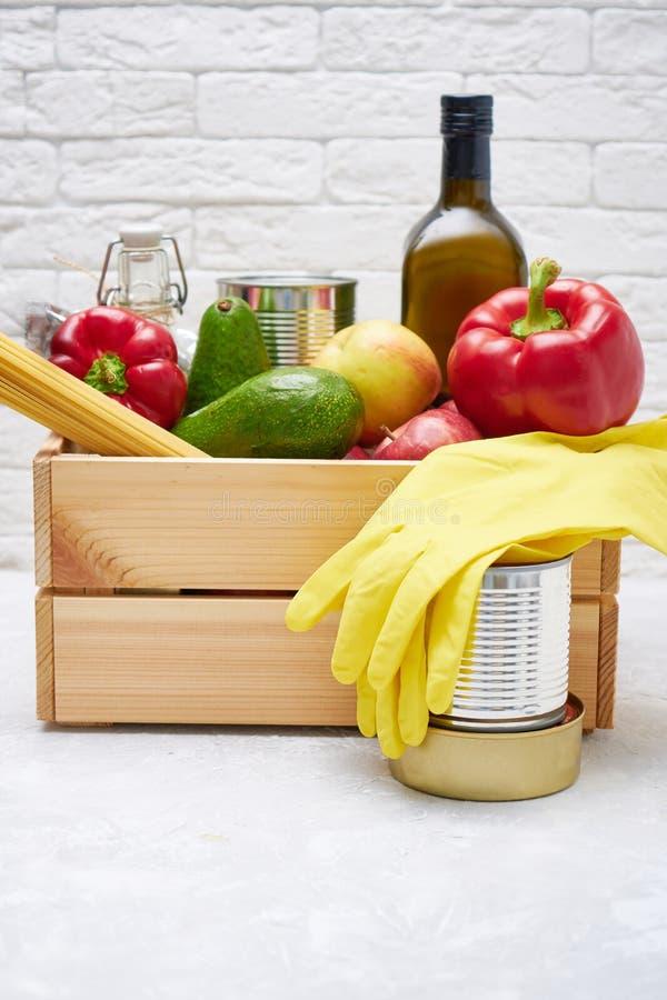Zapasy żywności w drewnianym pudełku Warzywa, olej, owoce, żywność w puszkach, makarony Dawstwo, dostarczanie żywności, koronawir zdjęcia royalty free