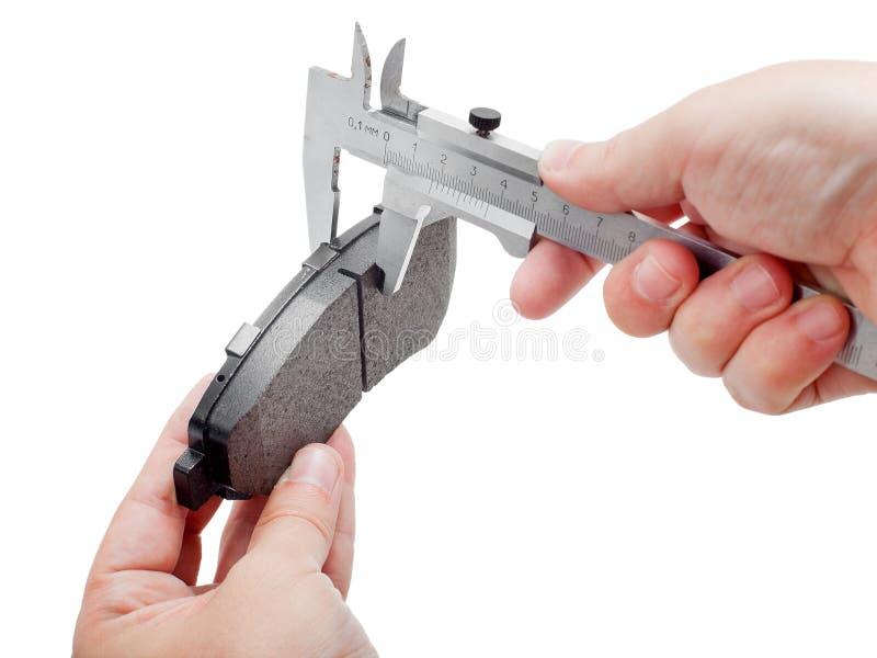 Zapatas de freno con el calibrador en la mano del ingeniero fotografía de archivo