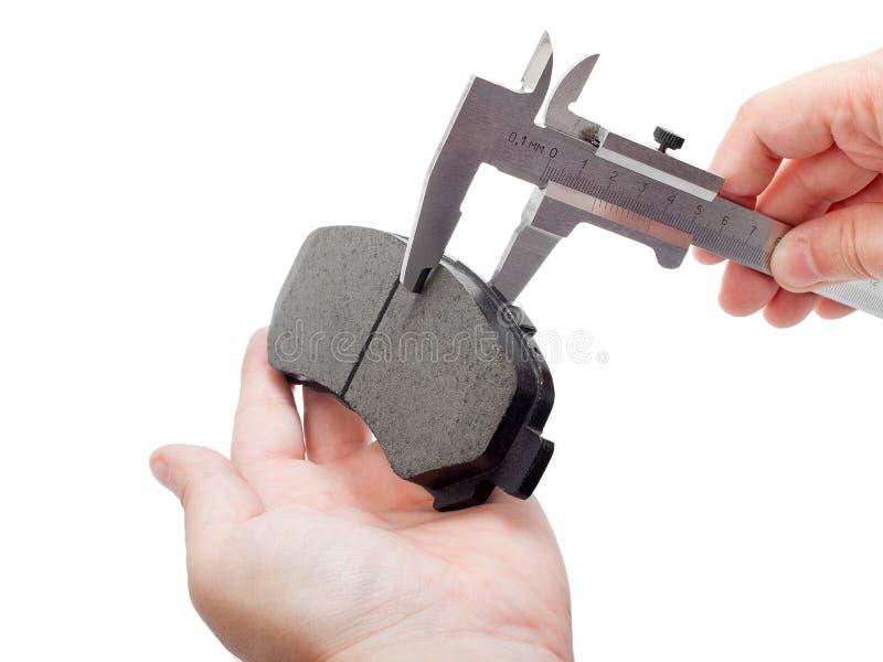 Zapatas de freno con el calibrador en la mano del ingeniero imagen de archivo