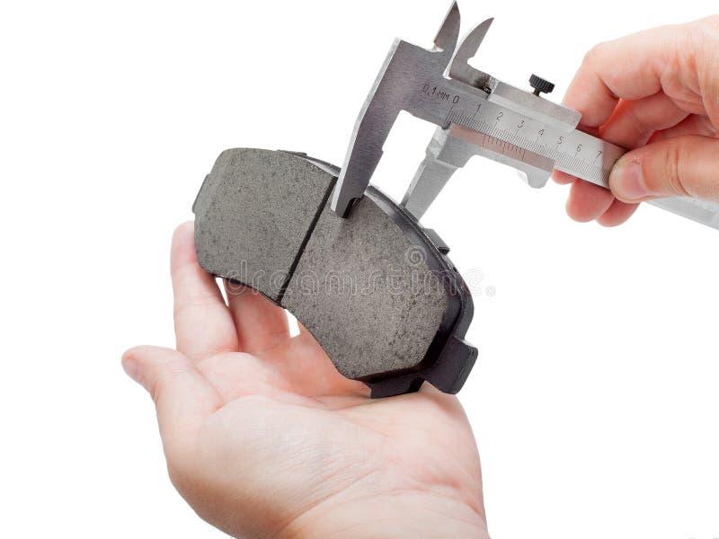 Zapatas de freno con el calibrador en la mano del ingeniero fotos de archivo libres de regalías