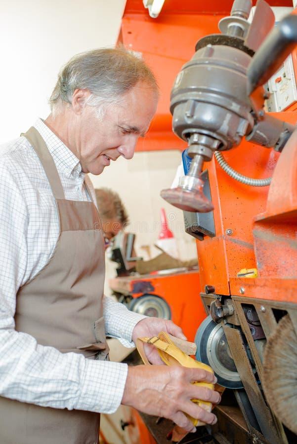 Zapatero que usa la maquinaria en el zapato del talón fotos de archivo libres de regalías