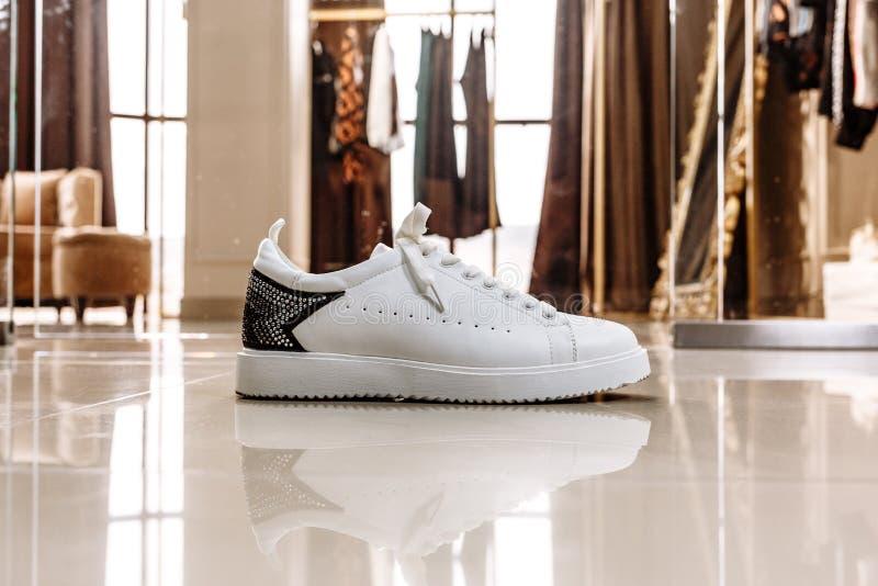 Zapatilla de deporte blanca con un ornamento de la estrella hecho de diamantes artificiales en el contexto en el piso ligero fotos de archivo libres de regalías