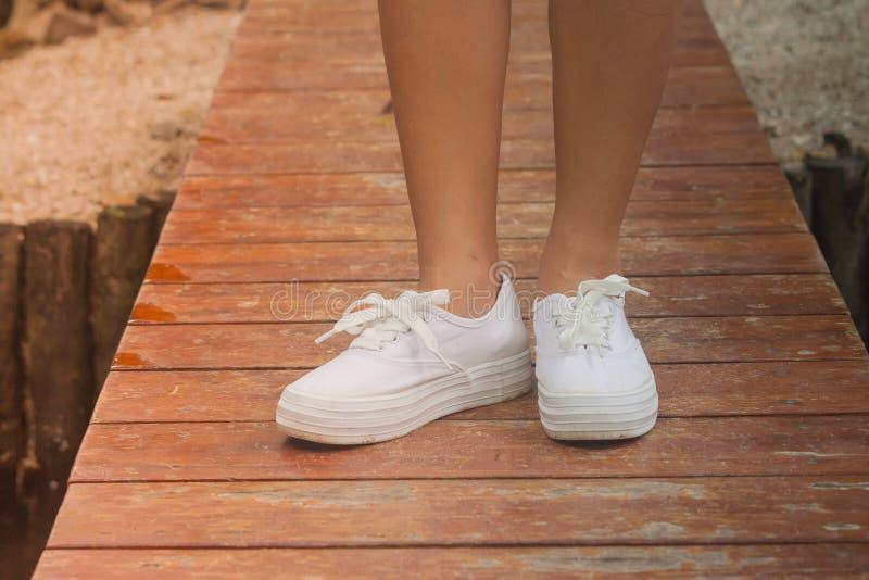 Zapatilla de deporte blanca y situación del desgaste de mujer en el puente de madera sobre el río imágenes de archivo libres de regalías