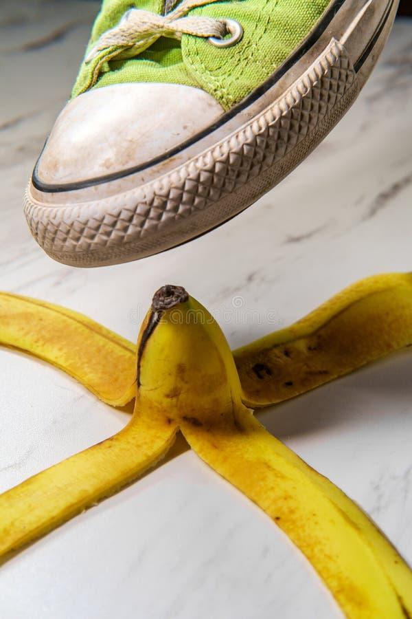 Zapatilla de deporte resbaladiza de la cáscara del plátano fotos de archivo