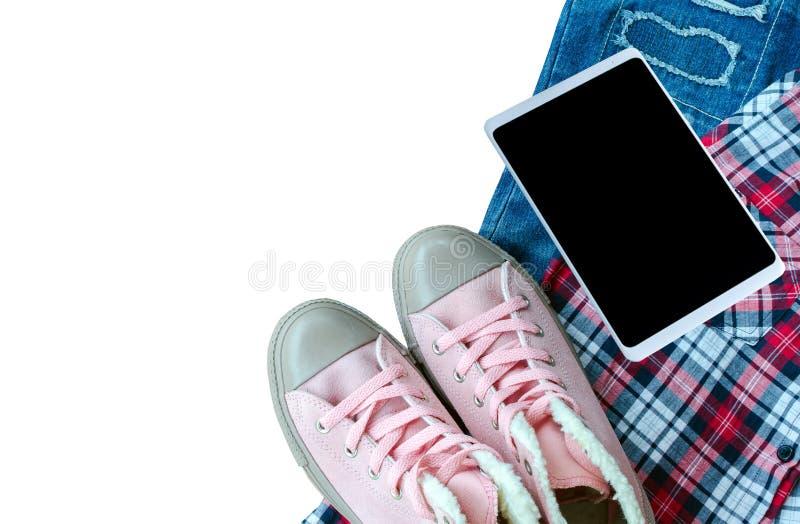 Zapatilla de deporte rosada, camisa de scott, mezclilla rasgada, Smart-teléfono aislado en wh fotos de archivo libres de regalías