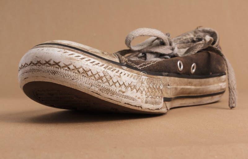 Zapatilla de deporte sucia vieja imagenes de archivo