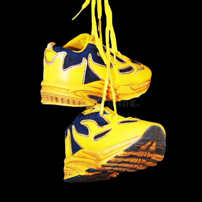 Zapatillas de deporte amarillas del bebé aisladas en fondo negro foto de archivo