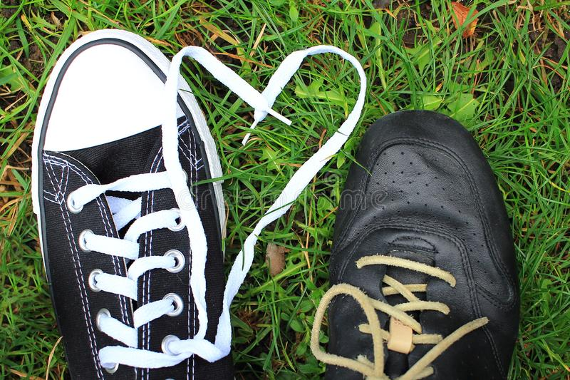 Zapatillas de deporte de amor de los pares en un fondo de los cordones de la hierba bajo la forma de corazón fotos de archivo libres de regalías