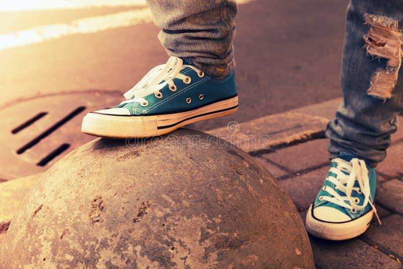 Zapatillas de deporte azules, pies del adolescente en los gumshoes, entonados fotos de archivo
