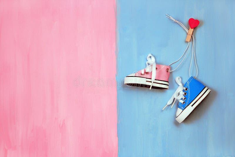 Zapatillas de deporte del bebé en concepto rosado y azul del fondo, del muchacho o de la muchacha imágenes de archivo libres de regalías