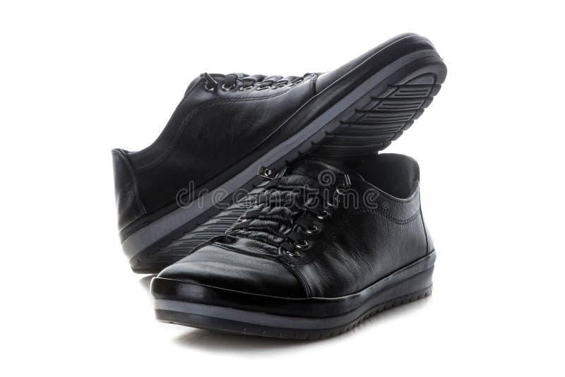 Zapatillas de deporte del ` s de las mujeres negras Zapatos del `s de las mujeres En el fondo blanco fotografía de archivo libre de regalías