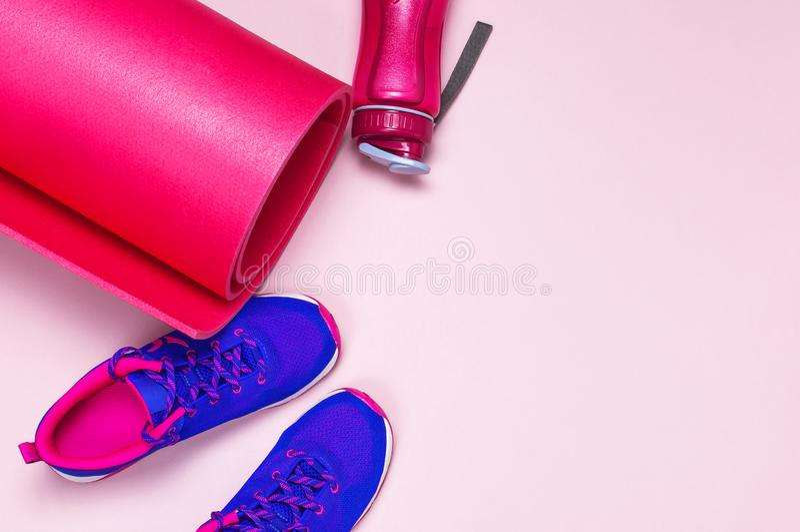Zapatillas de deporte femeninas rosadas violetas ultra azules, estera de la yoga, botella de agua en la opinión superior puesta p fotografía de archivo
