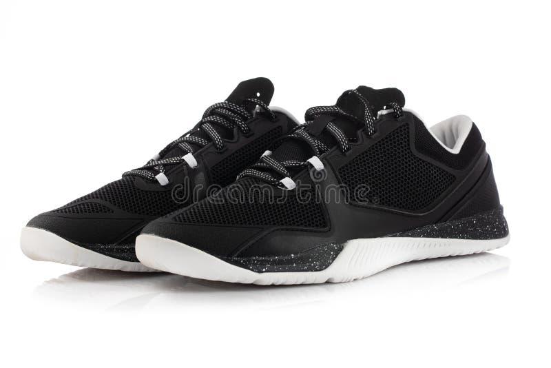 Zapatillas de deporte negras de la aptitud Zapatos del deporte en el fondo blanco foto de archivo