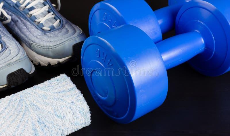 Zapatillas de deporte, pesas de gimnasia y una toalla en un fondo oscuro imágenes de archivo libres de regalías