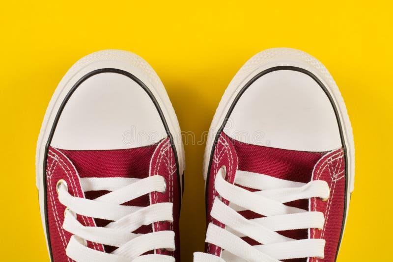 Zapatillas de deporte rojas en fondo retro de la tela vieja imagen de archivo libre de regalías