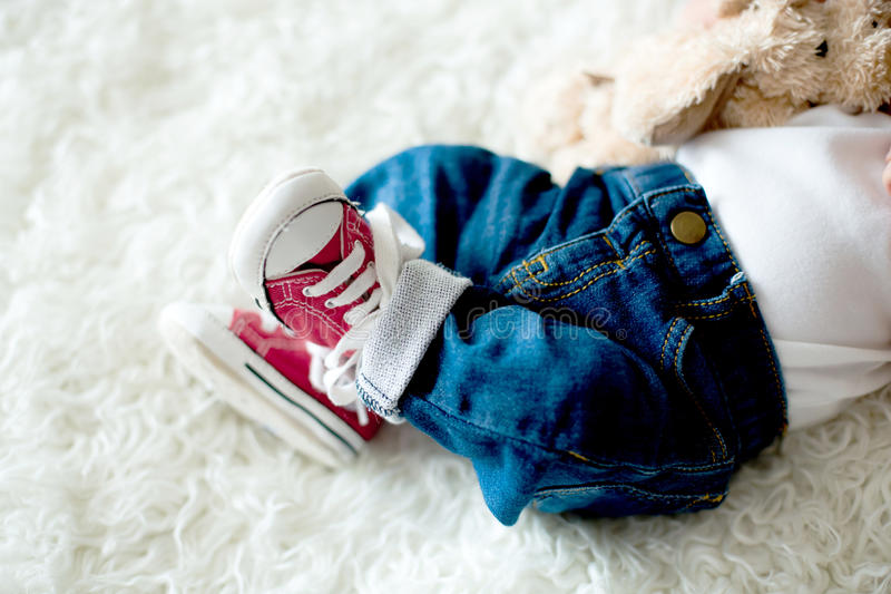 Zapatillas de deporte rojas de moda en pequeños pies recién nacidos de los bebés imágenes de archivo libres de regalías