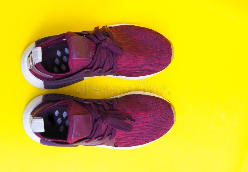Zapatillas de deporte rojas modernas de la moda de los pares aisladas en fondo amarillo imagen de archivo