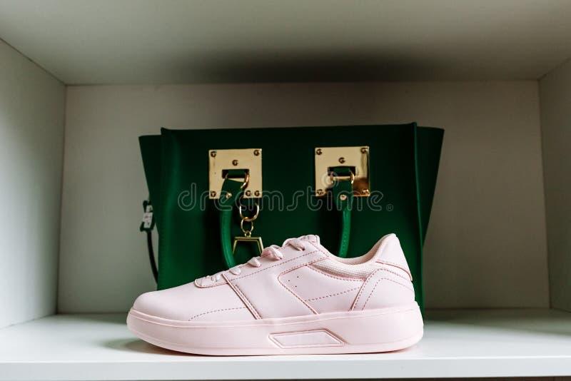 Zapatillas de deporte rosadas con los lenguados gruesos y un bolso verde en el fondo en el estante blanco de la tienda fotos de archivo libres de regalías