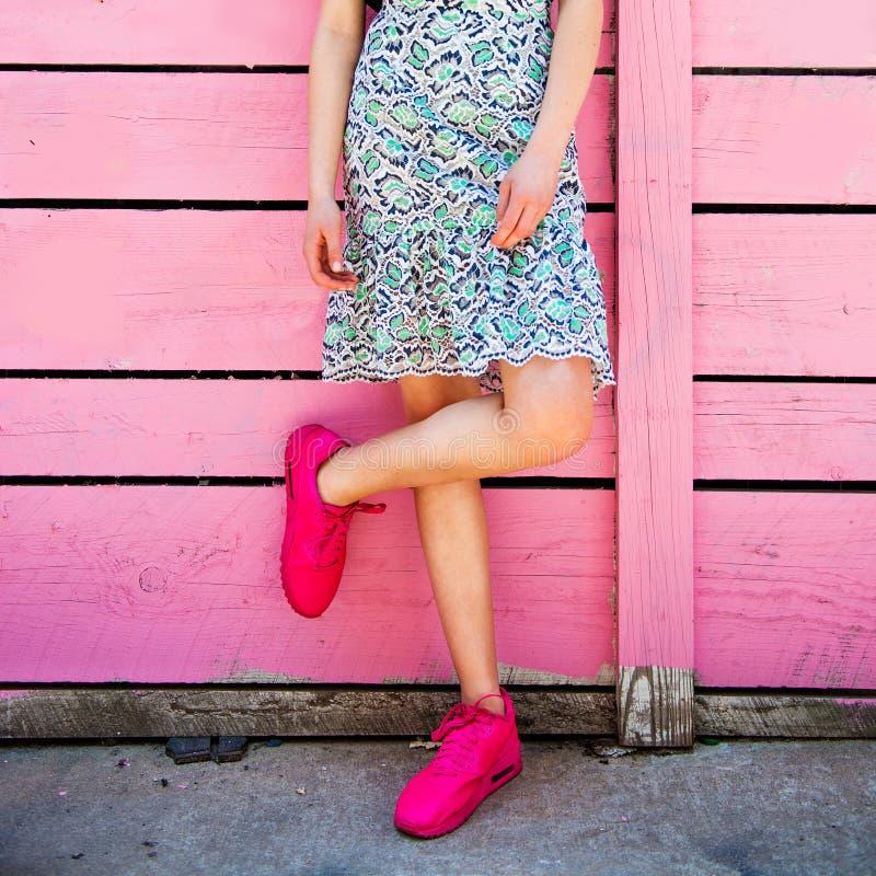 Zapatillas de deporte rosadas en las piernas de la muchacha en el fondo rosado de madera de la pared del grunge Estilo de la call fotos de archivo