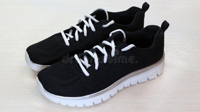 Zapatillas de deporte unisex del deporte negro con los cordones únicos y blancos blancos en el fondo blanco fotografía de archivo