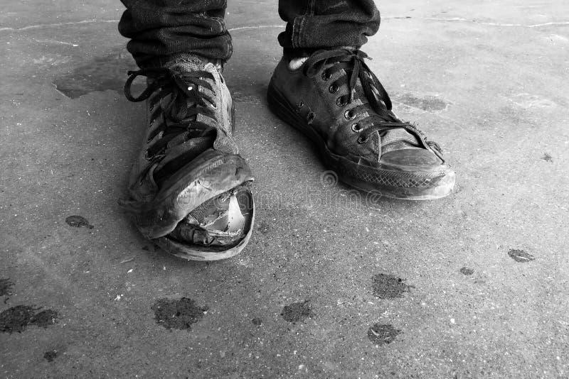 Zapatillas de deporte viejas quebradas del uso posterior del trabajador un rato largo en fotografía blanco y negro fotos de archivo