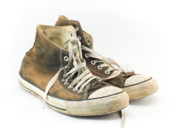 Zapatillas de deporte viejas y sucias en blanco imágenes de archivo libres de regalías