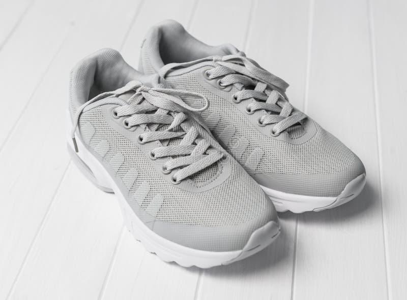 Zapatillas deportivas acogedoras grises que se sientan en la madera imagenes de archivo