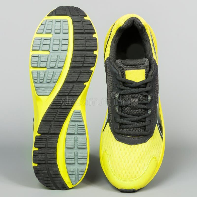 zapatillas deportivas amarillas con negro en fondo gris fotos de archivo