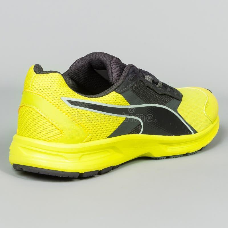 zapatillas deportivas amarillas con negro en fondo gris imagenes de archivo