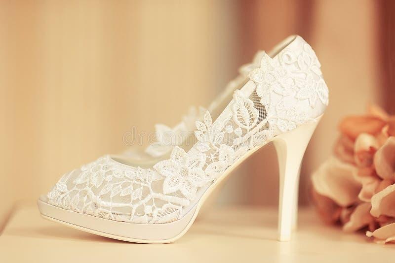 Zapato blanco de la boda del cordón y flores anaranjadas imágenes de archivo libres de regalías