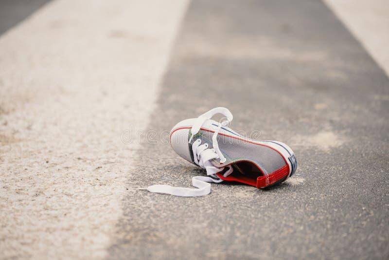 Zapato del ` s del niño en la calle después del incidente peligroso del tráfico imagen de archivo libre de regalías