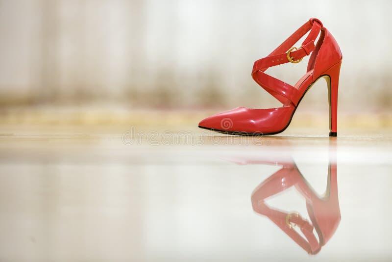 Zapato femenino del recorte rojo de cuero de moda del tacón alto con las hebillas de oro aisladas en fondo ligero del espacio de  imagen de archivo