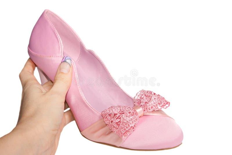 Zapato rosado del satén en una mano de la mujer aislada fotos de archivo