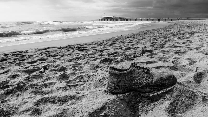 Zapato viejo en la arena imagenes de archivo