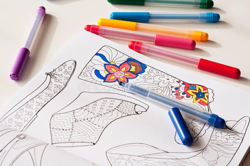 Zapatos abigarrados del modelo y plumas del fieltro del color en la tabla stock de ilustración