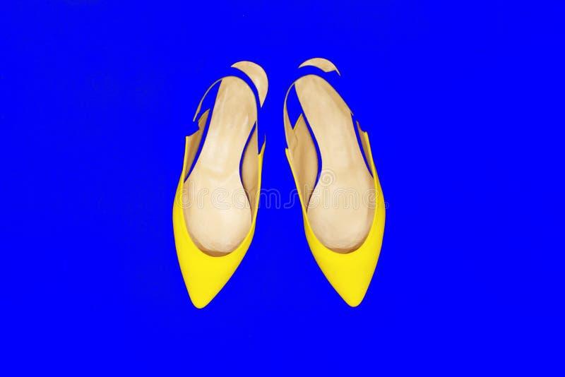 Zapatos amarillos de la moda del encanto en fondo de neón azul m?nimo Art Colorful Style brillante Se?ora brillante de lujo del p imagen de archivo libre de regalías