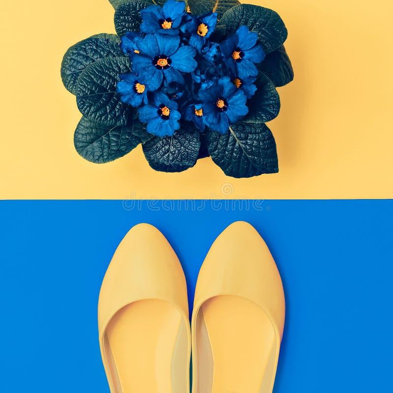 Zapatos amarillos y flores azules fotos de archivo