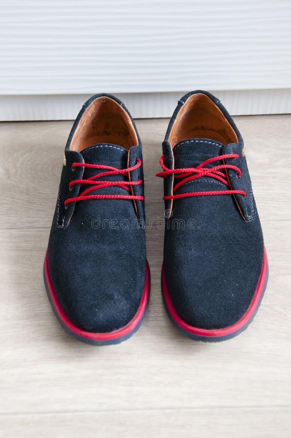 Zapatos azules del ante con los cordones rojos foto de archivo libre de regalías