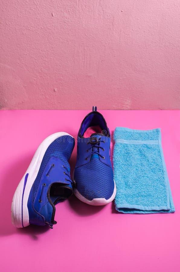 Zapatos azules en un fondo rosado aislado, toalla azul de los deportes para los deportes accesorios fotos de archivo