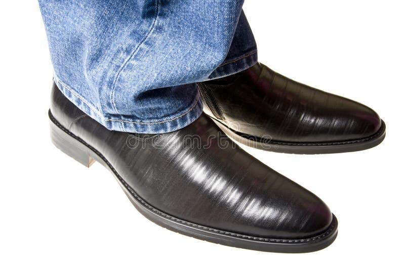 Zapatos bajo los pantalones vaqueros fotografía de archivo