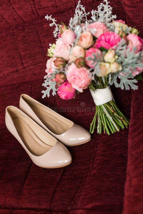 Zapatos beige de la boda de la moda femenina en foco con el ramo elegante del ` s de la novia en tonos en colores pastel desenfoc imagen de archivo libre de regalías