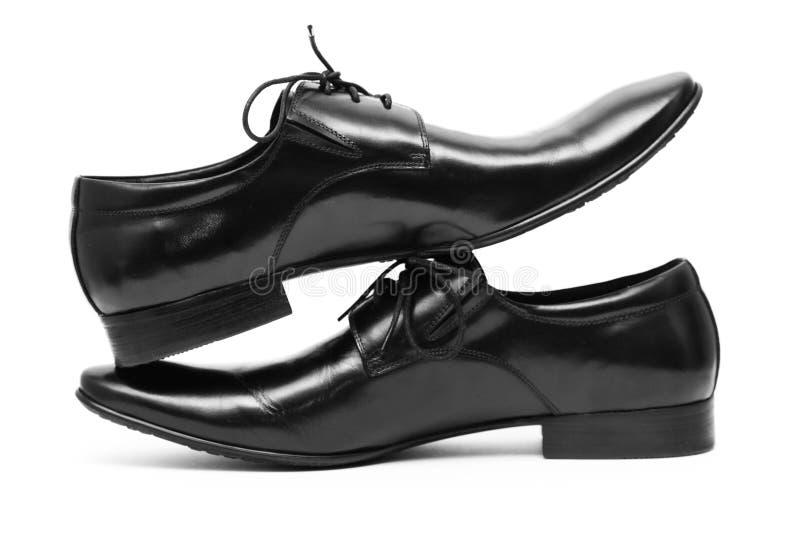 Zapatos clásicos de los hombres negros que se colocan en uno a imagenes de archivo