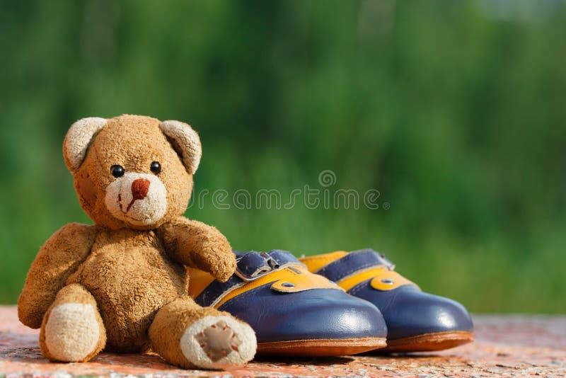 Zapatos de bebé con el oso de peluche imagenes de archivo